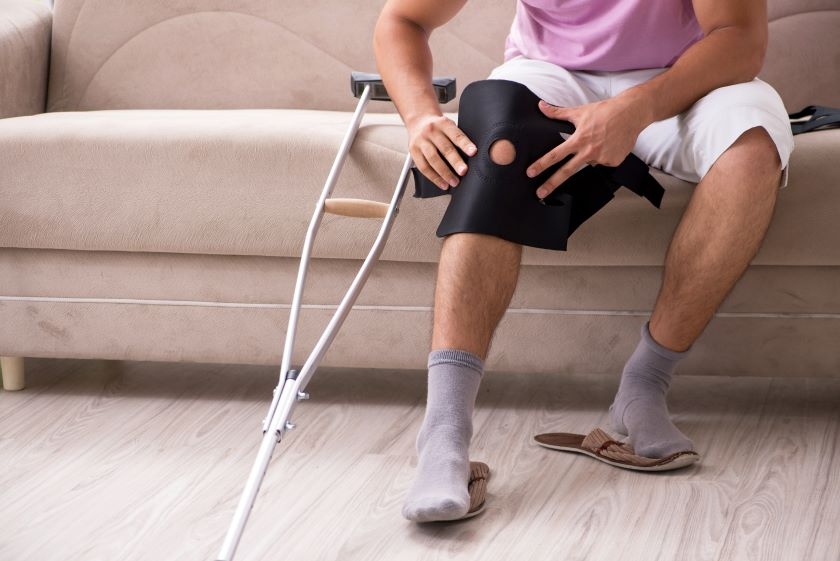 Man sitting on a couch with a crutch and knee brace